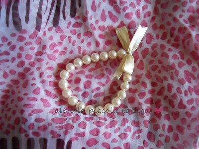 Bracciale con perline bianche e fiocchetto