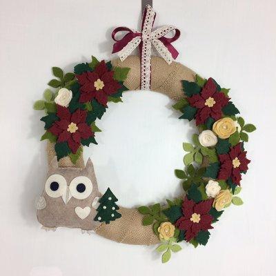 Ghirlanda natalizia con stelle di natale e gufo che porta un alberello
