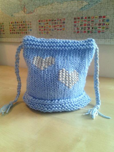 berretto per neonato in lana fatto a mano e ricamato con cuori e treccine laterali