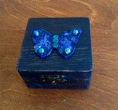 Scatolina blu con farfalla decorata.