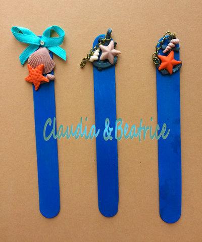 Segnalibri-segnaposto in legno decorati a mano in fimo a tema marino.