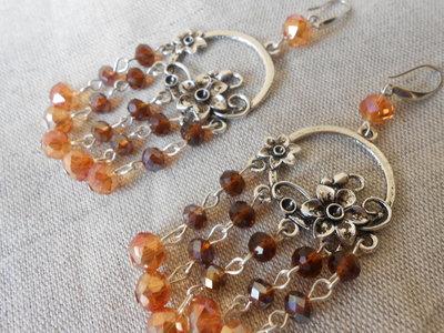 Orecchini chandelier con cristalli dorati di varie gradazione e motivo in metallo a forma di fiore.