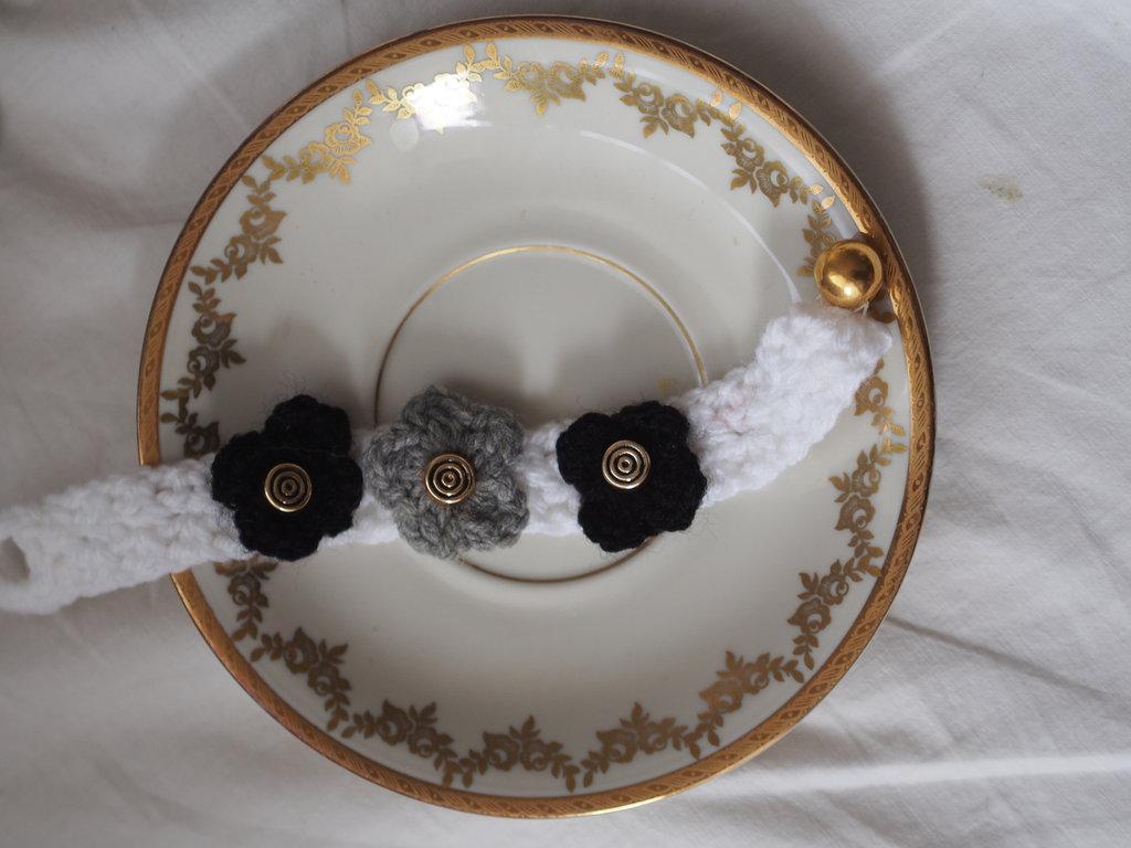 BRACCIALE a fascia in lana.Applicati tre fiori.UNCINETTO.(Bianco con fiori neri e grigi).Piccoli bottoncini dorati come dettaglio e sfera dorata quale chisura.