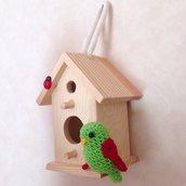 Casetta di legno con pappagallino amigurumi verde e rosso fatto a mano all'uncinetto