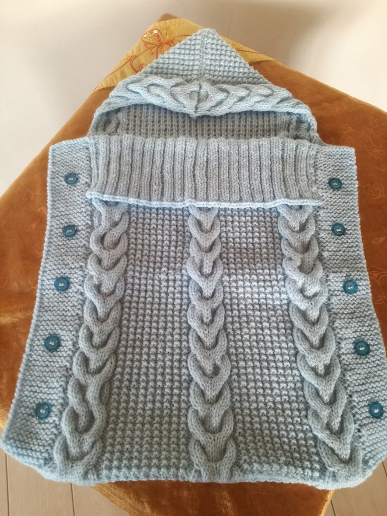 Copertina a sacco di lana con motivo a trecce, bottoni e cappuccio