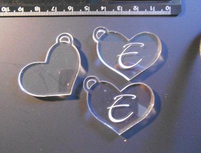 (165) Lotto 3 ciondoli a cuore in plexiglass trasparente con incisione